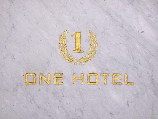 Michele Chiossi ONE HOTEL, 2006  marmo statuario, intarsio, foglia d'oro, ottone lucidato Alighiero Boetti tributo omaggio porta logo Kabul scultura